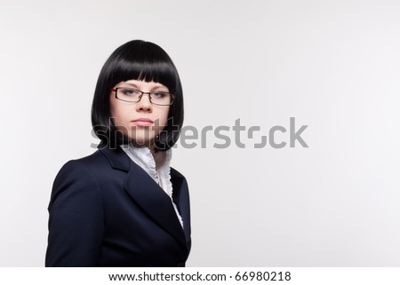 Close up  portrait of the beautiful young woman in a business suit and glasses on a light background