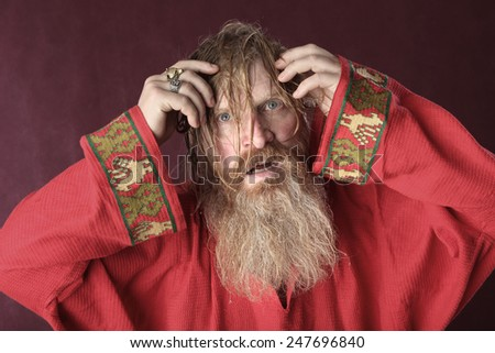 close-up portrait of the blessed with a long beard and a mustache and wet blond hair in a red shirt studio - stock photo