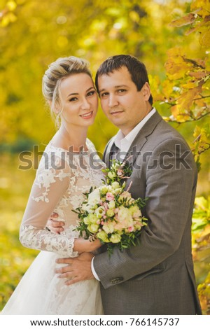 Close-up portrait of the bride and groom on a background of yellowing autumn leaves of the trees.