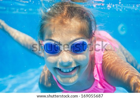 Close-up portrait of the cute girl swimming underwater and smiling