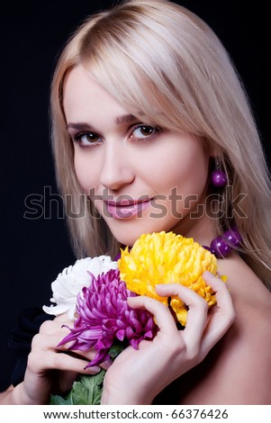 close up Portrait of the fine attractive young woman with flowers in hands on a black background