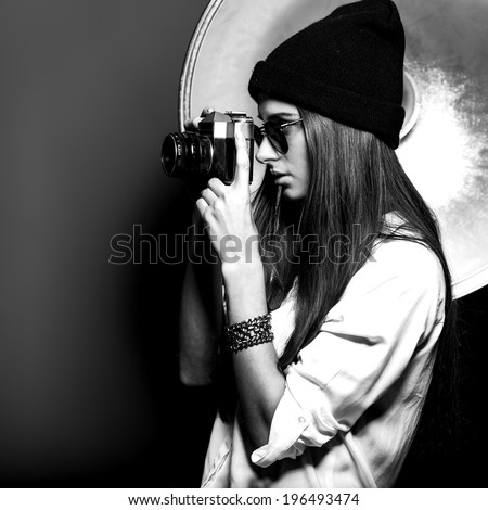 Close-up portrait of the photographer girl with glasses and hat - stock photo