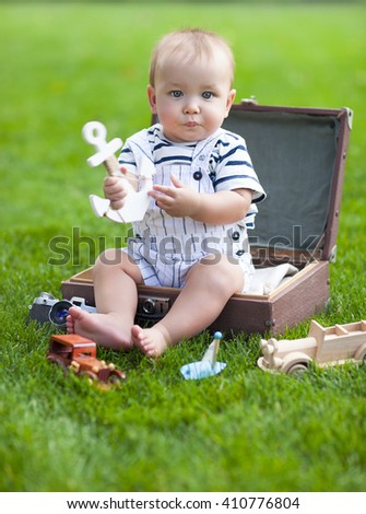 Close up portrait of the smiling baby boy playing outdoors. Holliday and travel concept - stock photo