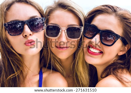 Close up portrait of three funny pretty young women smiling sending kiss and having fun in summer time, fresh fashion  portrait of girls friends wearing sunglasses. - stock photo