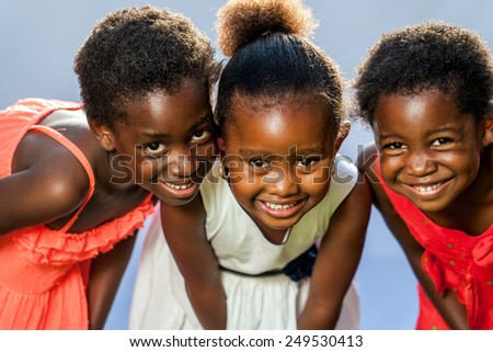 Close up portrait of three small happy African girls with heads together.
