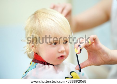 Close up portrait of toddler child getting his first haircut - stock photo