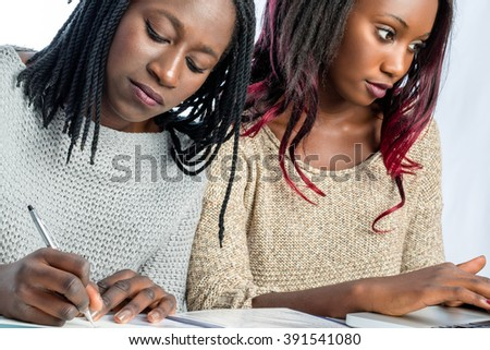 Close up portrait of two African female teen students working together at desk.Girls taking notes with pen and paper and typing on laptop. - stock photo