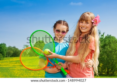 Close-up portrait of two beautiful girls with tennis racquets standing in flower field