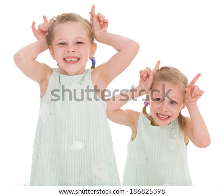 Close-up portrait of two cheerful children lying at home, happy family, love and friendship concepts - stock photo