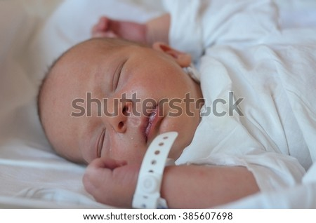 Close up portrait of two days old newborn boy in a hospital - stock photo