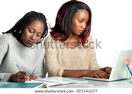 Close up portrait of two female african teen students working doing homework together.Girl with braids hair writing with pen in notebook and another girl typing on laptop.Isolated on white background.