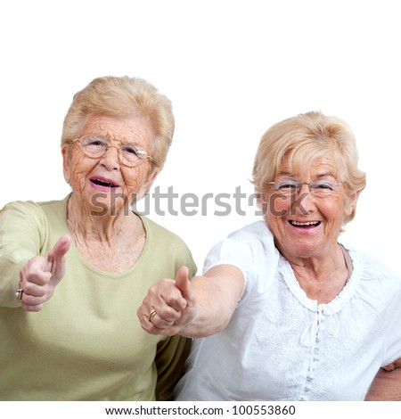 Close up portrait of two friendly senior women showing thumbs up.Isolated on white. - stock photo
