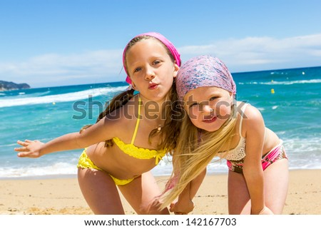 Close up portrait of two girlfriends in swimwear on beach.