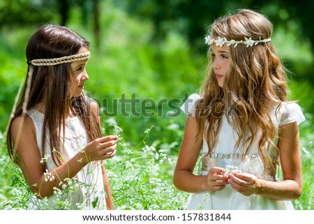 Close up portrait of two girls standing in flower field. - stock photo