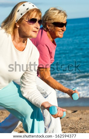 Close up portrait of two golden age women doing early morning workout on beach.