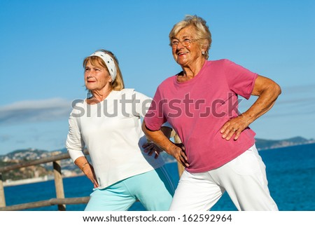Close up portrait of two golden age women stretching together outdoors. - stock photo