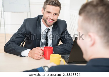 Close-up portrait of two handsome businessmen in suits having a coffee-break in office sitting at the table, with selective focus on one smiling businessman and another sitting back to the camera - stock photo