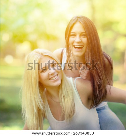 Close up portrait of two happy girls hugging outdoors - stock photo