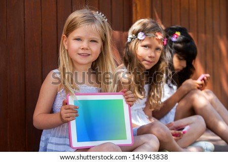 Close up portrait of two kids with tablet and smart phone outdoors. - stock photo
