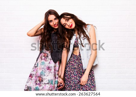 Close up   portrait of two pretty hipster  sisters  wearing boho colorful dress, stylish jeans jacket  and  baubles. Girls smile, have fun against  urban white wall. - stock photo