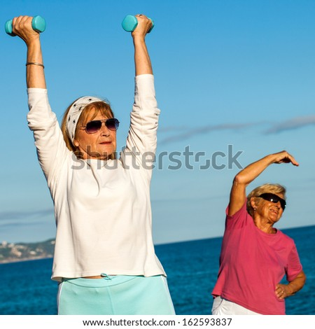Close up portrait of two senior ladies working out with weights on beach.