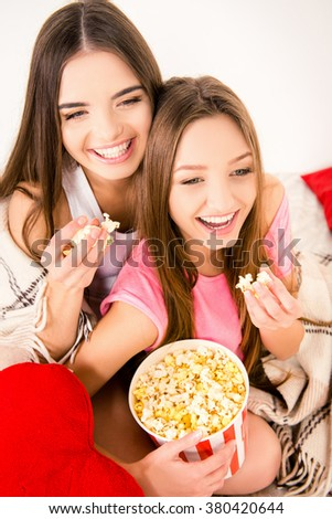 Close up portrait of two smiling young girl eating popcorn