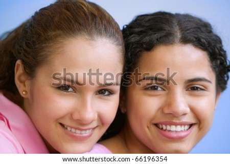 Close up portrait of two teenage girls smiling - stock photo