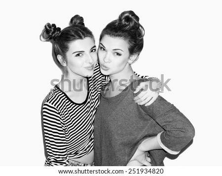 Close up portrait of two young girl having fun and hugging. Top knot hairdo. White background, not isolated. Inside - stock photo