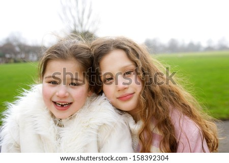Close up portrait of two young girls children sisters sitting on a bench in a park during a cold winter day holding their heads together and smiling joyfully, outdoors. - stock photo