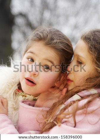 Close up portrait of two young girls children sisters together in a park during a cold winter day, with one whispering secrets into the others ear, smiling outdoors. - stock photo
