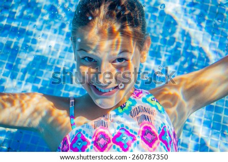 Close-up portrait of underwater happy cute girl in swimming pool - stock photo