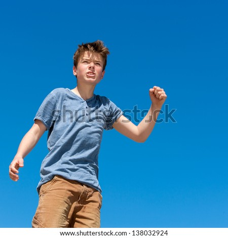 Close up portrait of upset boy raising fist outdoors. - stock photo