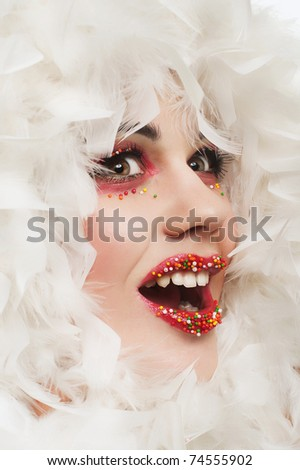 close up portrait of white woman with candies on her lips and boa