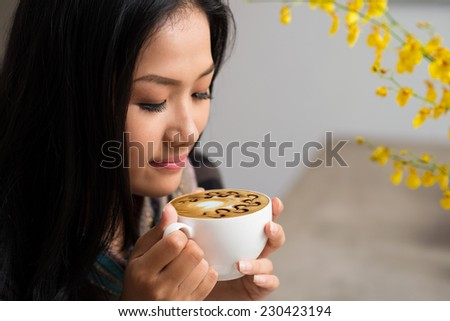 Close-up portrait of woman enjoying morning cappuccino - stock photo