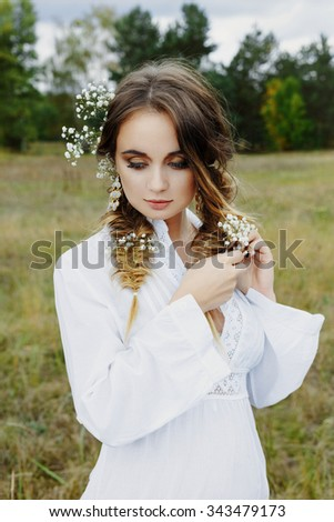 Close up portrait of woman face with floral white flowers in hair outdoors