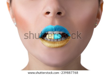 close-up portrait of woman face with perfect skin and mouth with coloured pill between teeth - stock photo