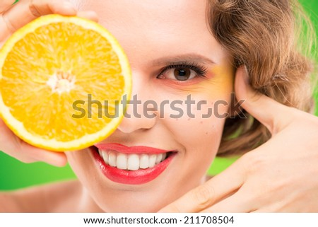 Close-up portrait of woman holding a half of orange - stock photo