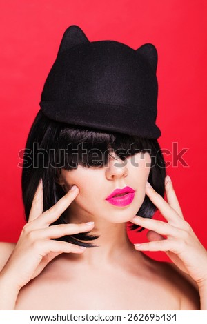 Close up portrait of woman in cat hat. Cap with animal ears. on red background - stock photo