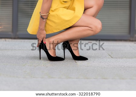 Close-up portrait of woman's legs on high heels. Lady in yellow dress sitting and touching her right leg near office building. - stock photo