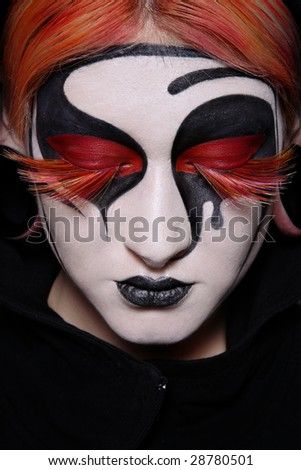 Close-up portrait of woman with faceart and fancy false lashes - stock photo