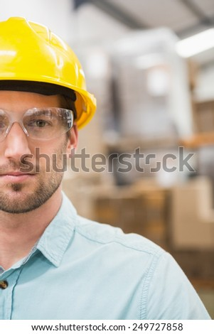 Close up portrait of worker wearing hard hat in the warehouse - stock photo