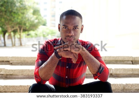 Close up portrait of young african man sitting outdoors on steps and staring at camera