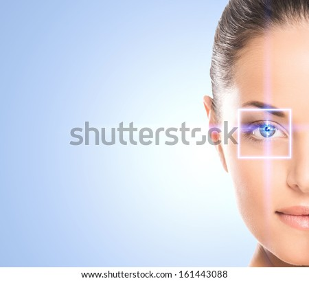 Close-up portrait of young and beautiful woman with the virtual hologram on her eyes (laser medicine and security technology concept) - stock photo