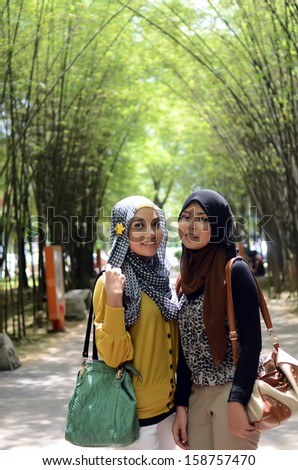 Close-up portrait of young Asian Muslim girl smiles - stock photo