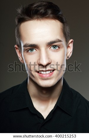 close up portrait of young attractive man with nice smile isolated on dark background looking at camera