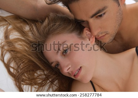 Close up portrait of young attractive romantic couple hugging and kissing, laying down on a white bed, having sex and being loving with each other. Love and relationships lifestyle, interior bedroom. - stock photo
