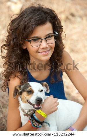 Close up portrait of young attractive teenage girl with her dog outdoors. - stock photo