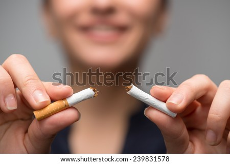 Close up portrait of young attractive woman breaking down cigarette to pieces. Studio shot selective focus isolated on grey. Addiction concept - stock photo