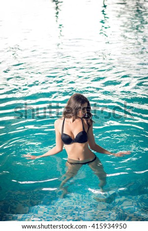 Close up portrait of young attractive woman enjoying swimming in indoor pool. Wellness resort interior.