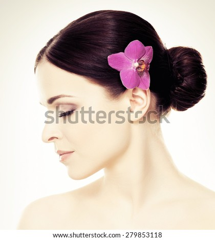 Close-up portrait of young, beautiful and healthy woman with an orchid flower in her hair isolated on white - stock photo